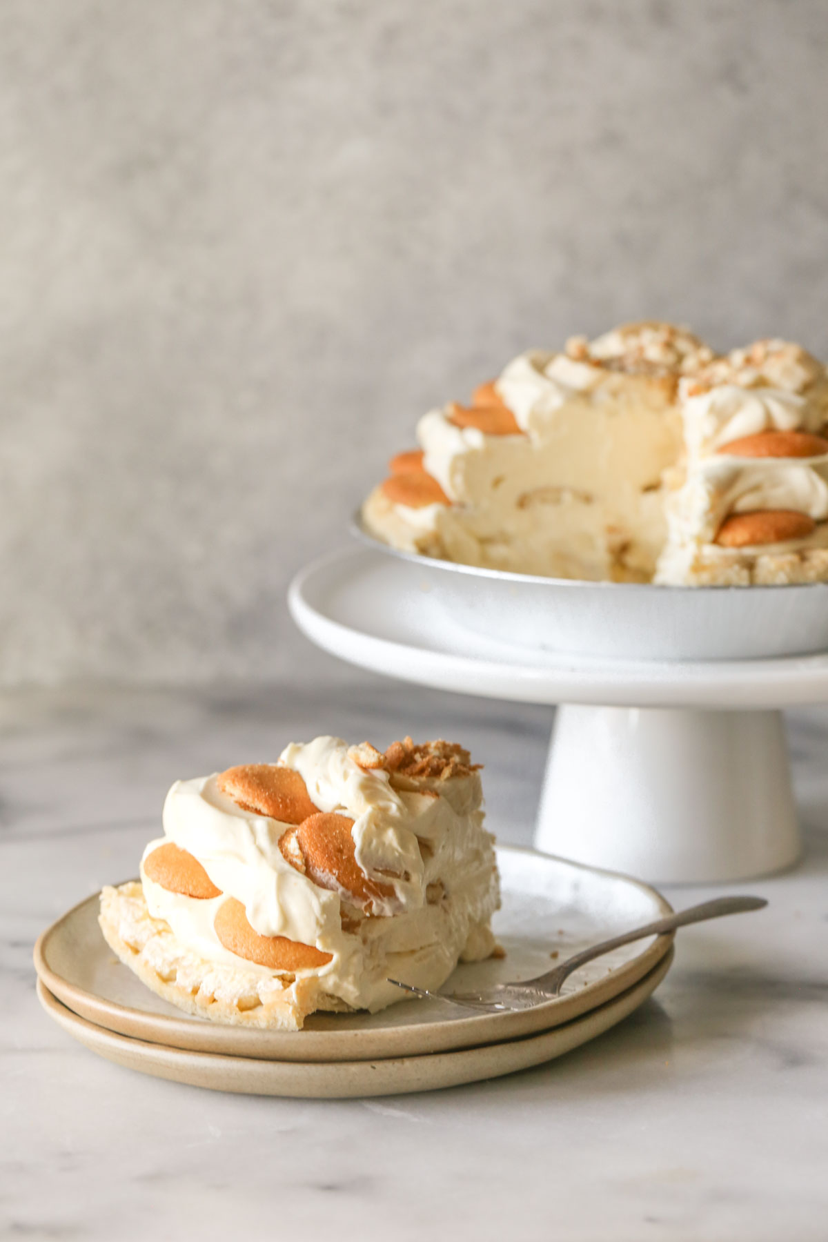 A piece of Mile High Banana Pudding Pie on a plate with a fork, and the rest of the Mile High Banana Pudding Pie on a white cake stand in the background.