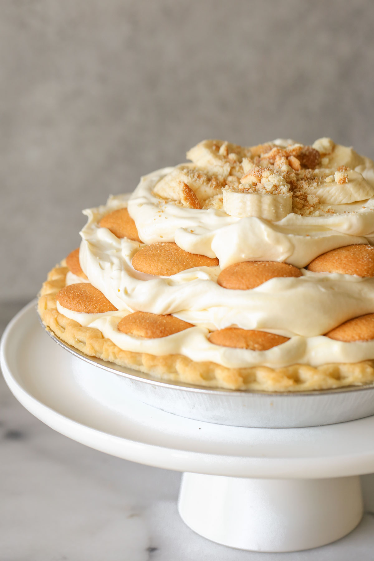 Mile High Banana Pudding Pie on a white cake stand.