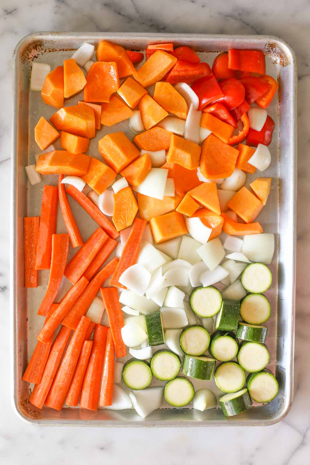 Overhead shot of the prepared squash, carrots, zucchini, pepper and onion on a baking sheet before being roasted for the Roasted Vegetable Soup.