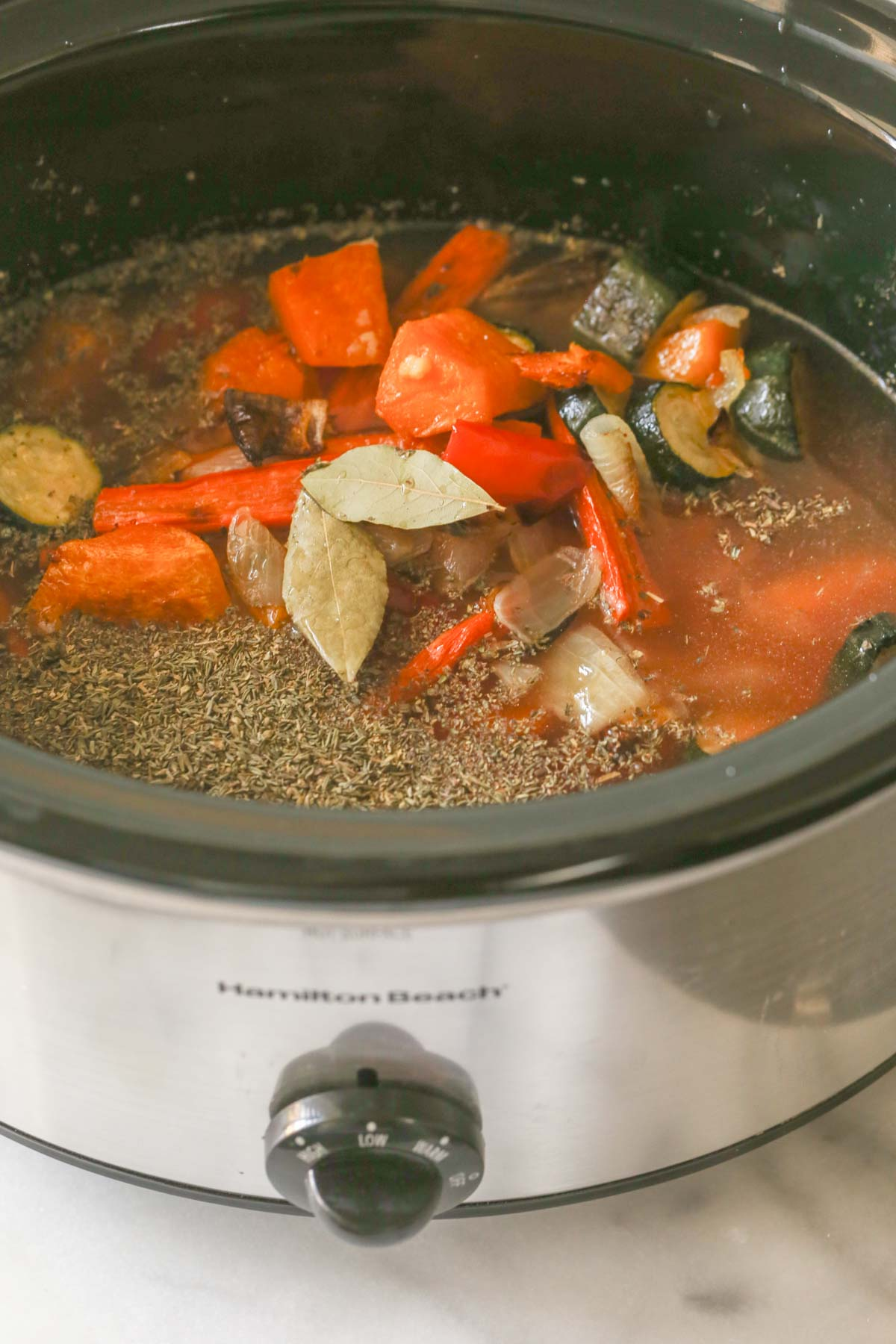 A crockpot with all the ingredients for the Roasted Vegetable Soup in it.