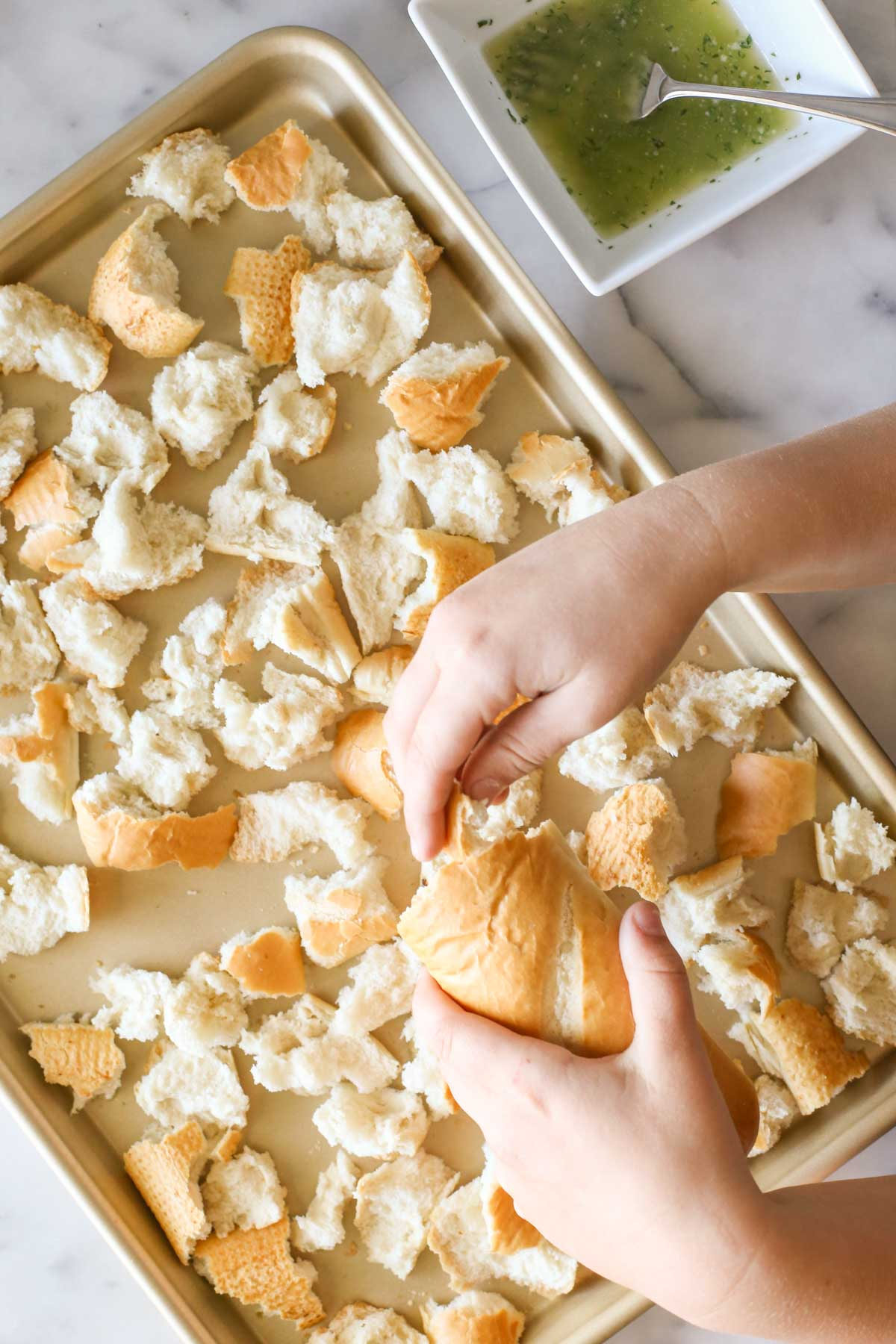 Overhead shot of a hand tearing the French bread into pieces over a baking sheet, with a square bowl of the butter mixture next to the baking sheet.