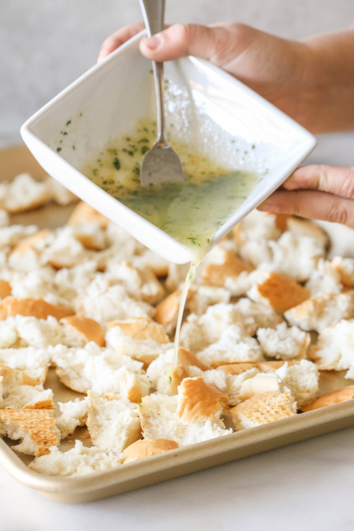 The butter mixture in a square bowl being poured over the French bread pieces on the baking sheet to make Rustic Buttery Garlic Croutons.