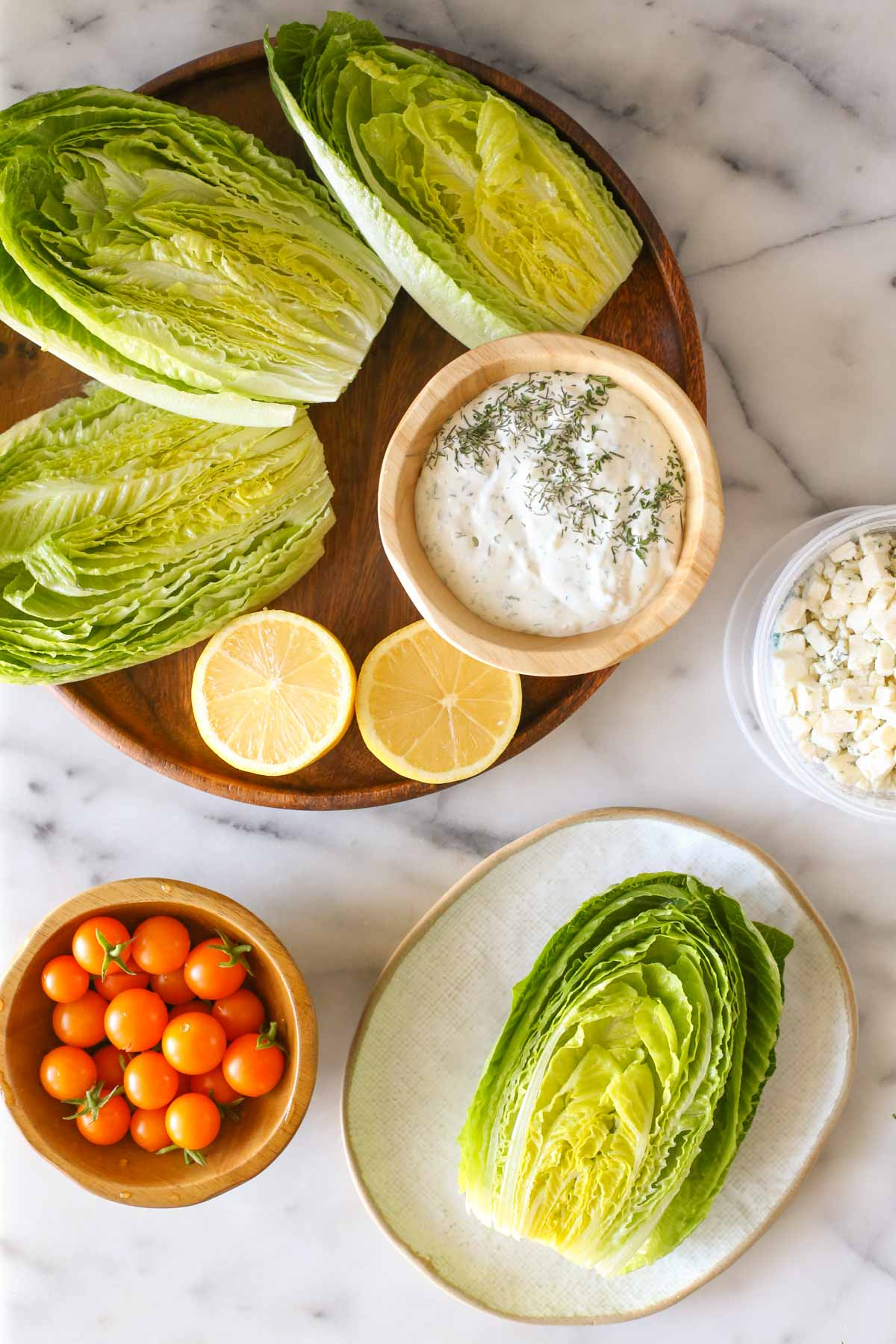 Overhead shot of a wood platter with three romaine lettuce halves, lemon wedges and a wood bowl of the blue cheese dressing on it, sitting next to a wood bowl of Sungold tomatoes, a container of blue cheese and a plate with a romaine lettuce half on it, all on a marble background.