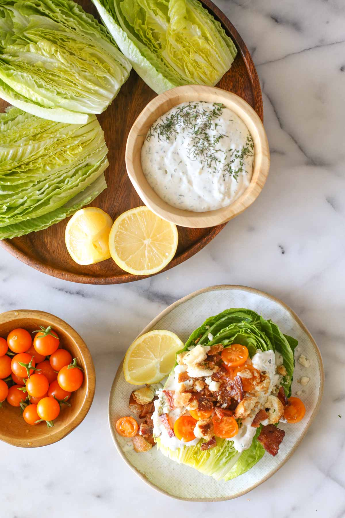 Overhead shot of a wood platter with three romaine lettuce halves, lemon wedges and a wood bowl of the blue cheese dressing on it, sitting next to a wood bowl of Sungold tomatoes, and a Wedge Style BLT Salad on a plate, all on a marble background.