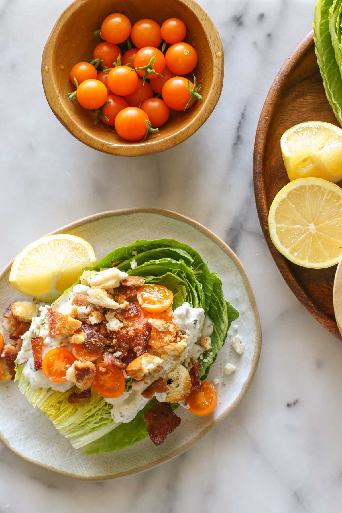 Overhead shot of a Wedge Style BLT Salad on a plate with a lemon wedge, next to a wood bowl of Sungold tomatoes and a wood platter with lemon wedges, all on a marble background.