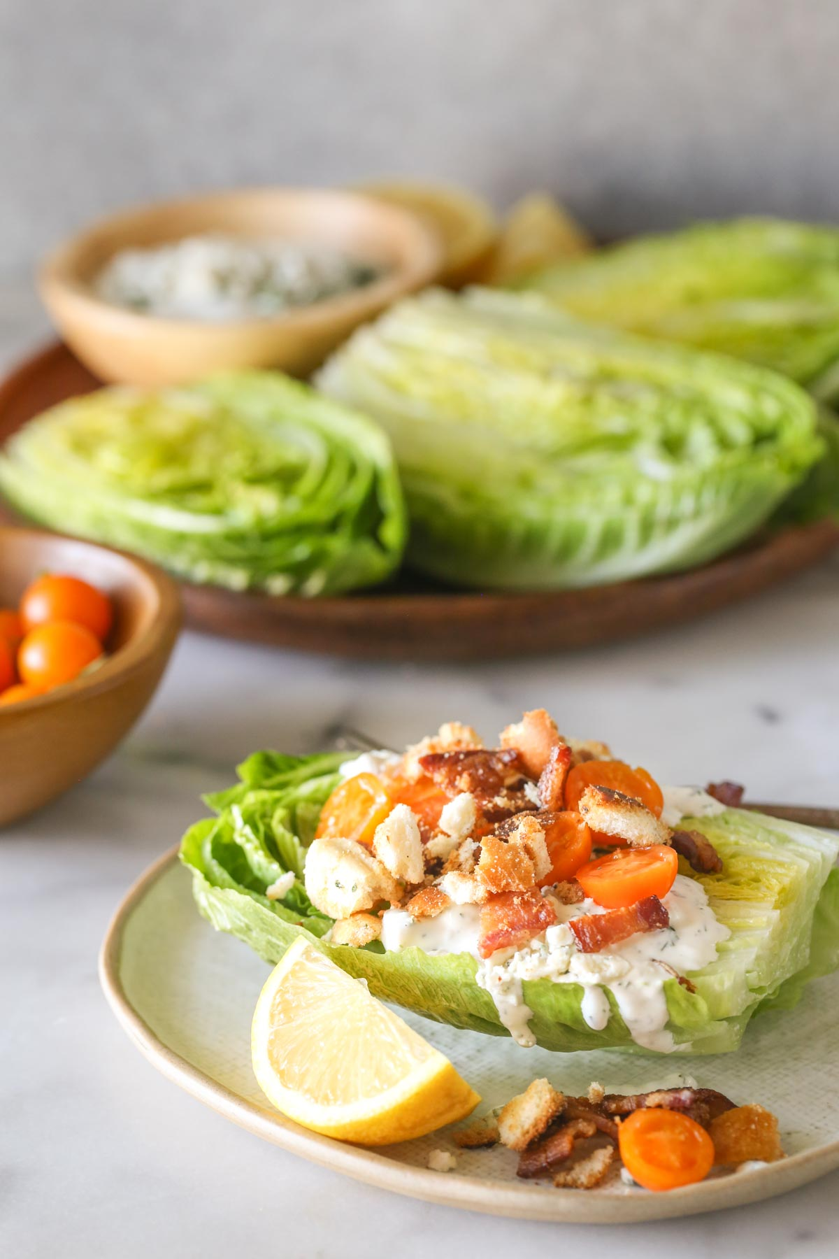 A Wedge Style BLT Salad on a plate with a lemon wedge, with a wood bowl of Sungold tomatoes and a wood platter with the romaine lettuce halves, a bowl of blue cheese dressing and lemon wedges on it in the background.