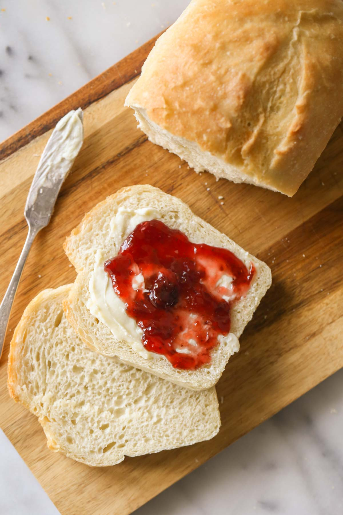 Overhead shot of a Sourdough Sandwich Loaf sliced on a cutting board with a butter knife next to the bread, and one of the slices of bread has butter and jelly on it.