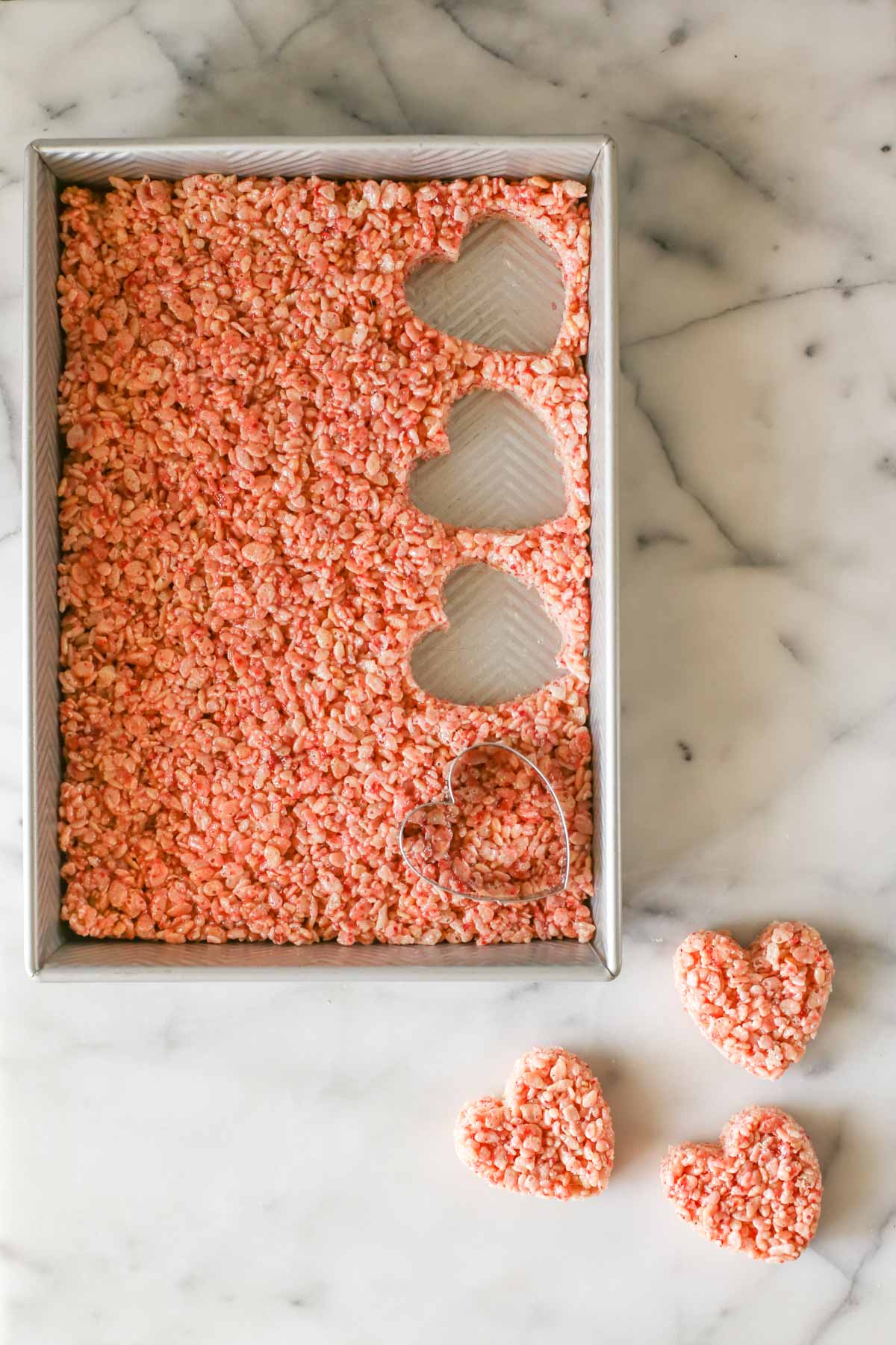 Overhead shot of a pan of Strawberry Rice Krispie Treats with a heart shaped cutter in the pan with three hearts already cut out and laying next to the pan, all on a marble background.