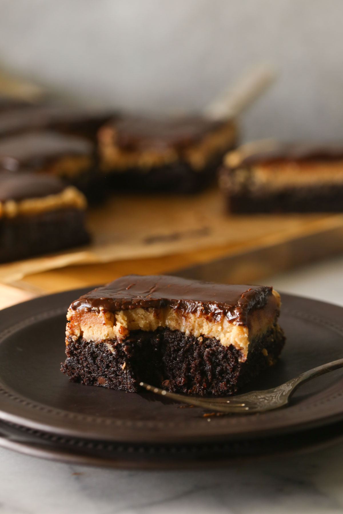 A Chocolate Peanut Butter Brownie on a plate with a fork, with more brownies in the background.