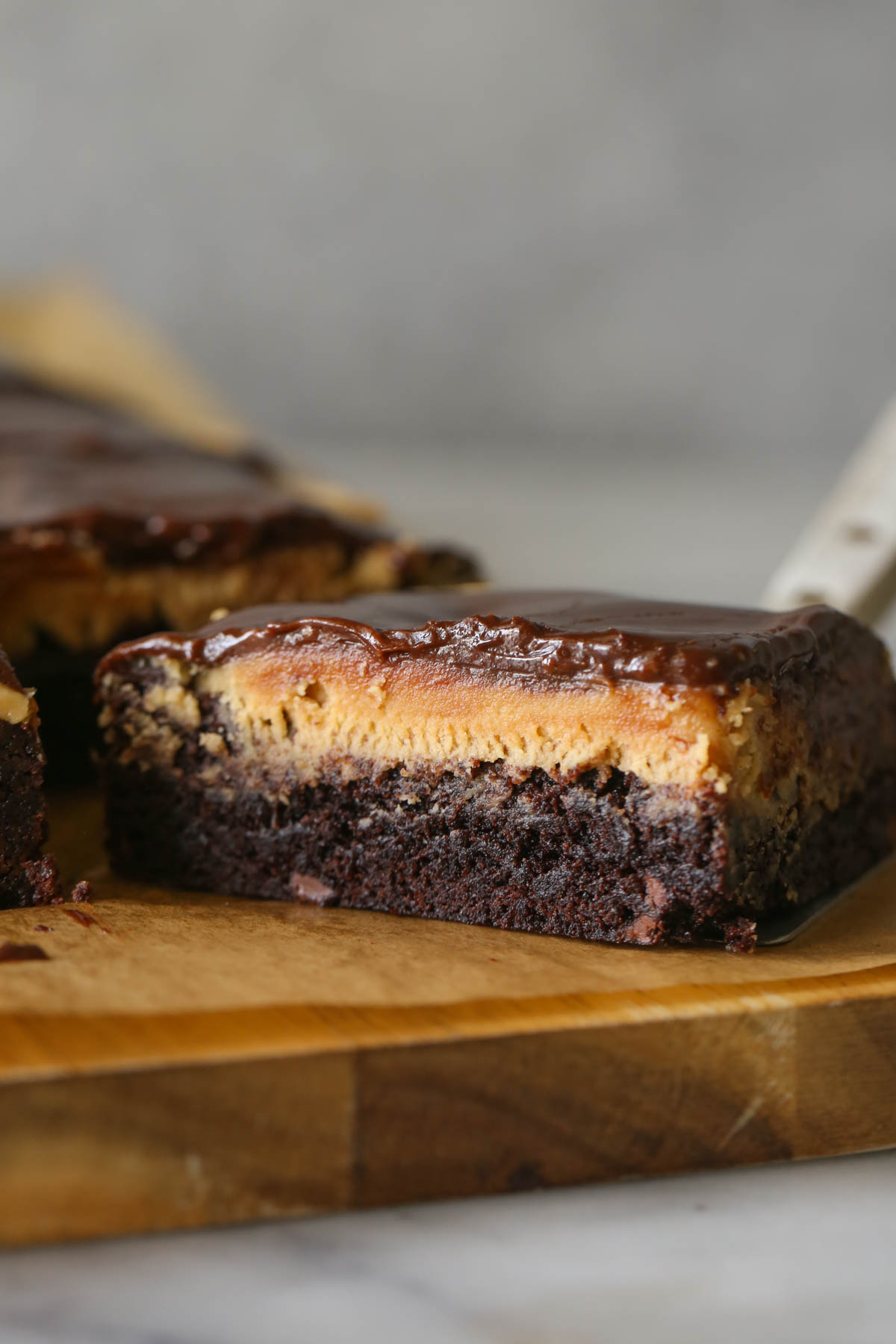 Close up shot of a cut piece of Chocolate Peanut Butter Brownie, showing the three layers.