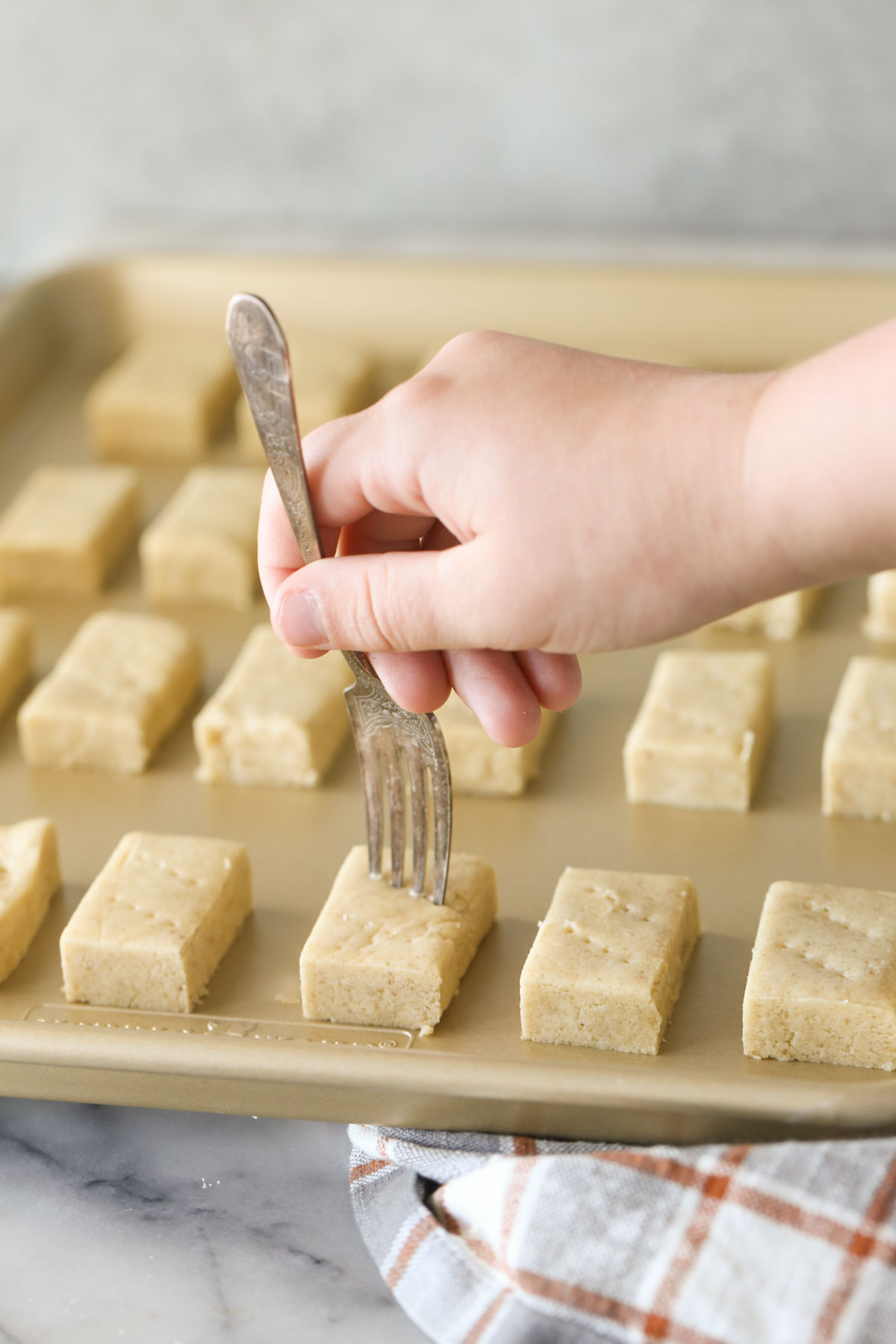 Buttery Shortbread Cookie dough rectangles arranged on a baking sheet, with a hand using a fork to poke the top of the dough.
