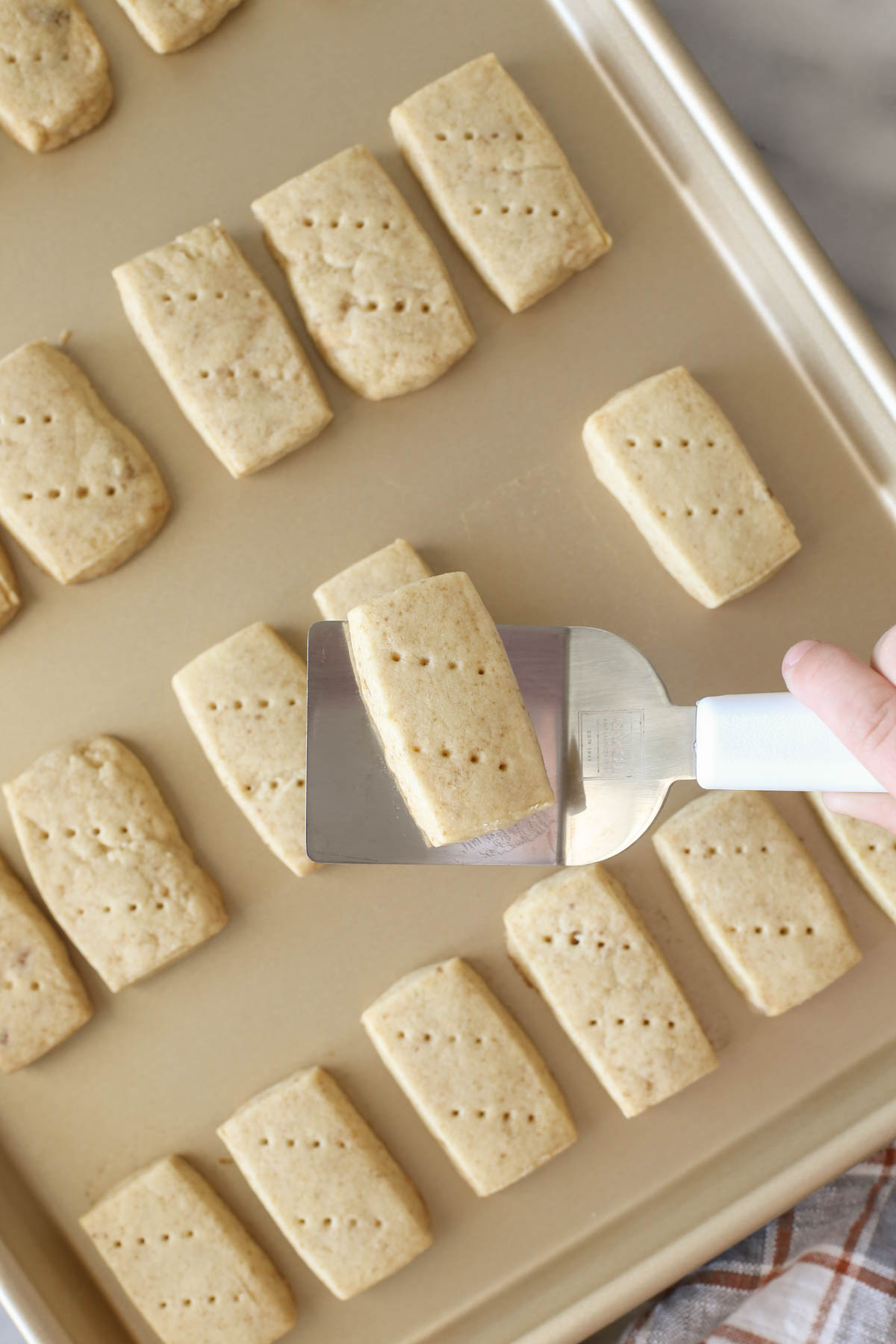 Overhead shot of a spatula with a Buttery Shortbread Cookie held over the baking sheet with more Buttery Shortbread Cookies.