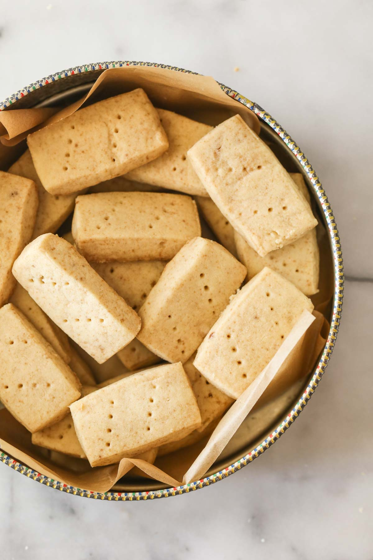 Overhead shot of a round cookie tin full of Buttery Shortbread Cookies.