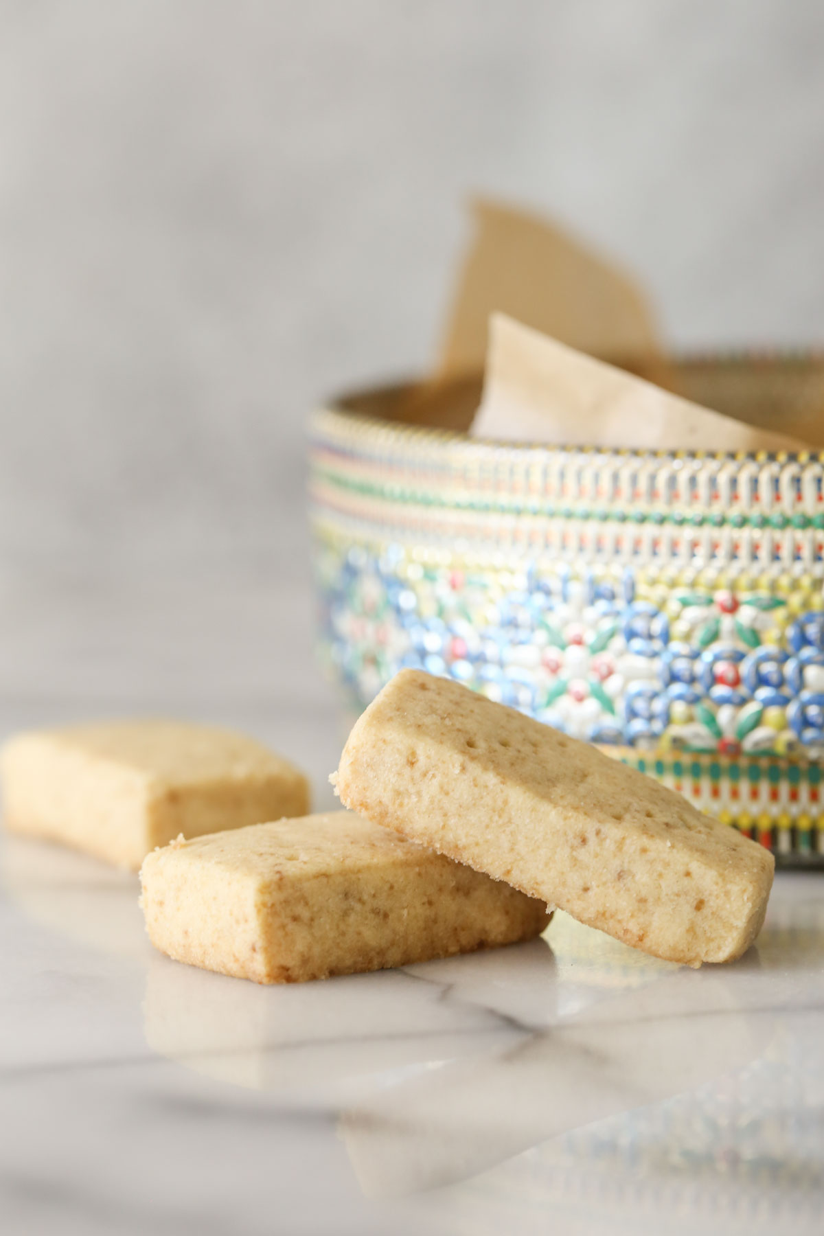 Close up shot of two Buttery Shortbread Cookies stacked, with another cookie in the background next to a colorful round cookie tin.