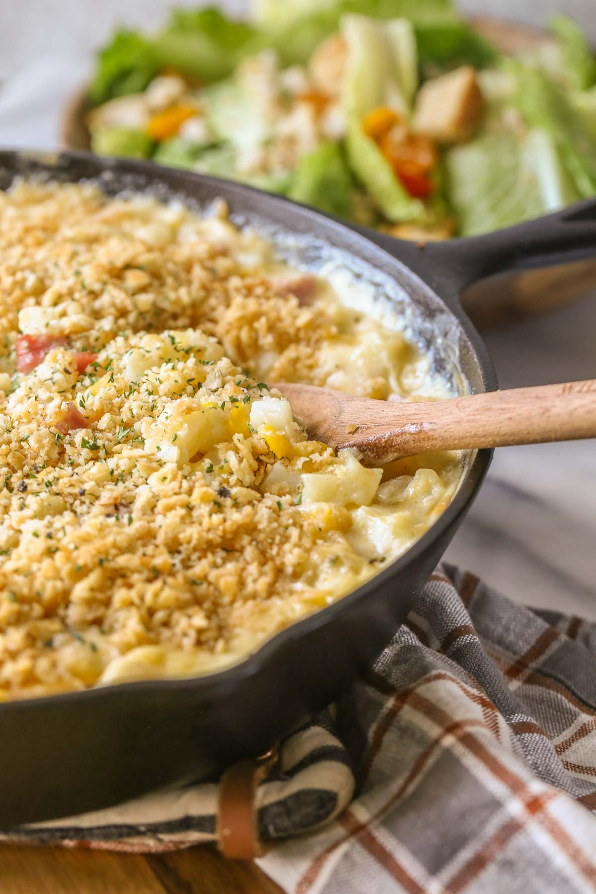 Close up shot of Cheesy Ham and Potato Skillet in a cast iron skillet with a wooden serving spoon in it, and a bowl of salad in the background.
