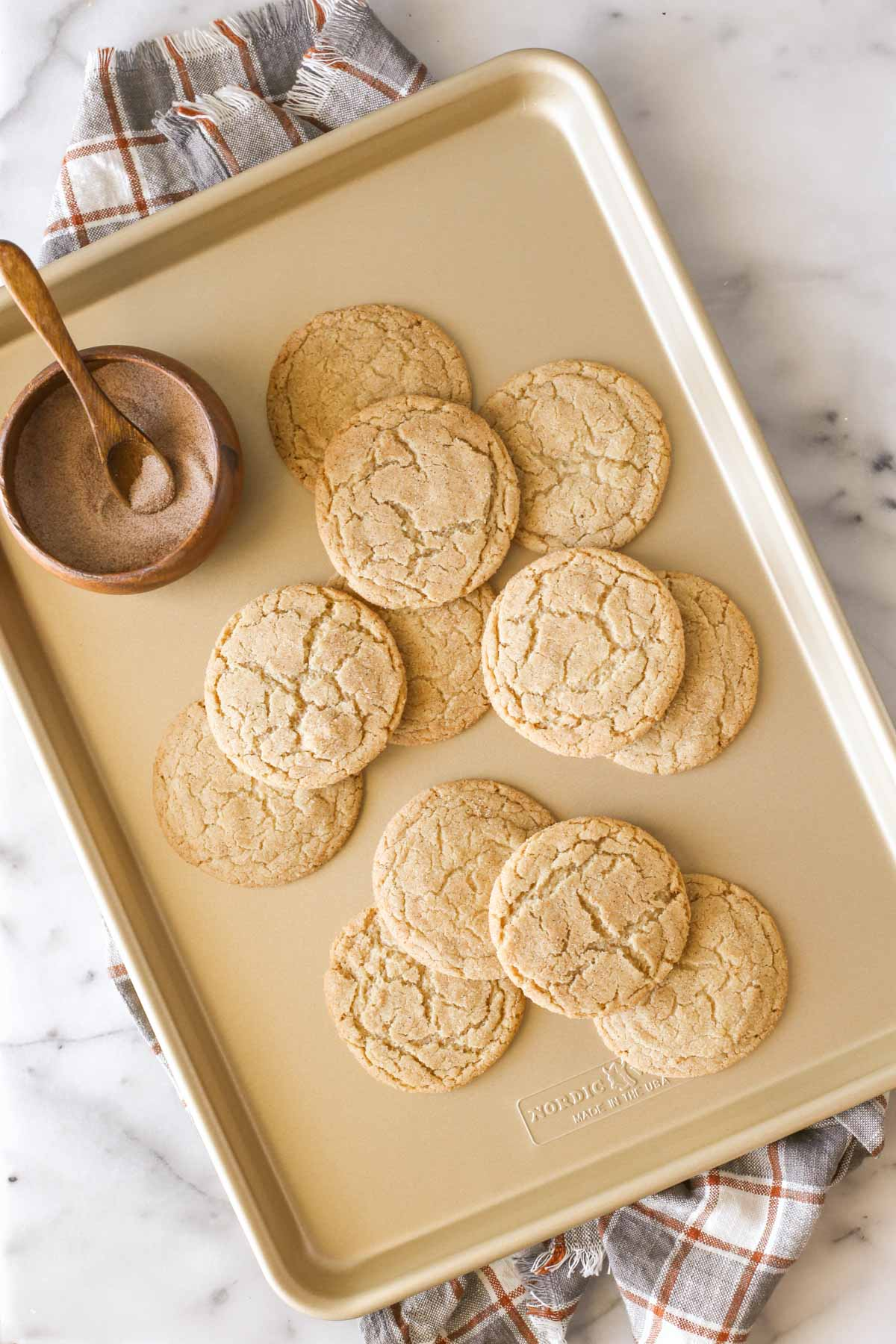 Overhead shot of Brown Butter Snickerdoodles on a baking sheet, along with a small wood bowl of cinnamon sugar with a small wooden spoon in it.