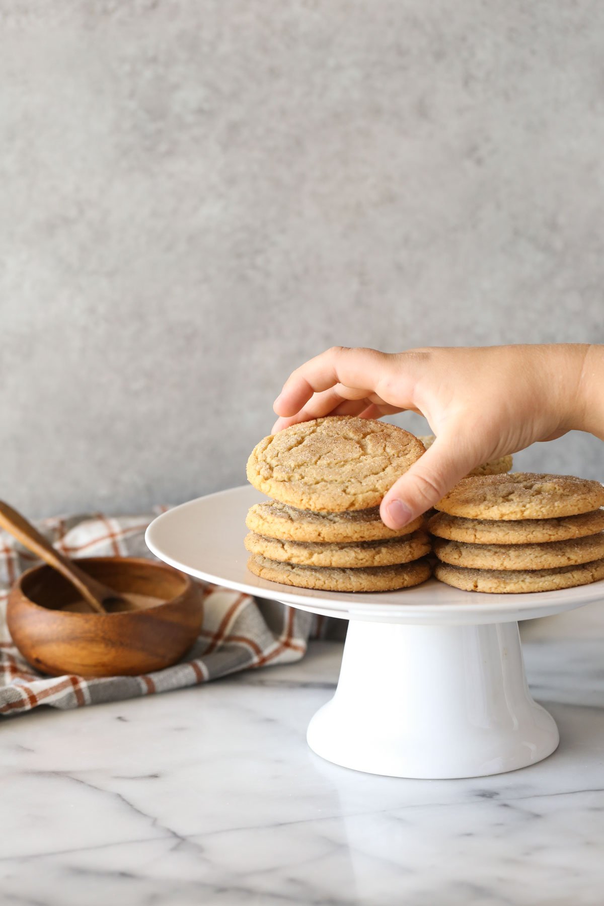 Brown Butter Snickerdoodles stacked on a white cake stand, with a hand picking up the cookie on top of one of the stacks, and a small wood bowl of cinnamon sugar in the background.