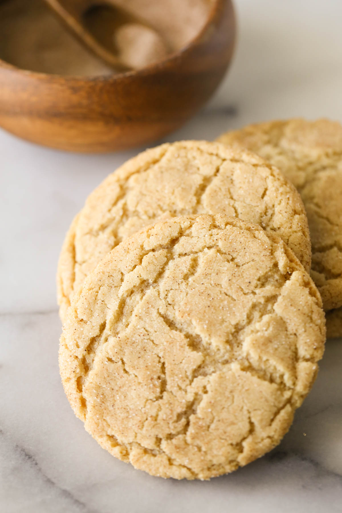 Close up shot of Brown Butter Snickerdoodles, with a small wood bowl of cinnamon sugar in the background.