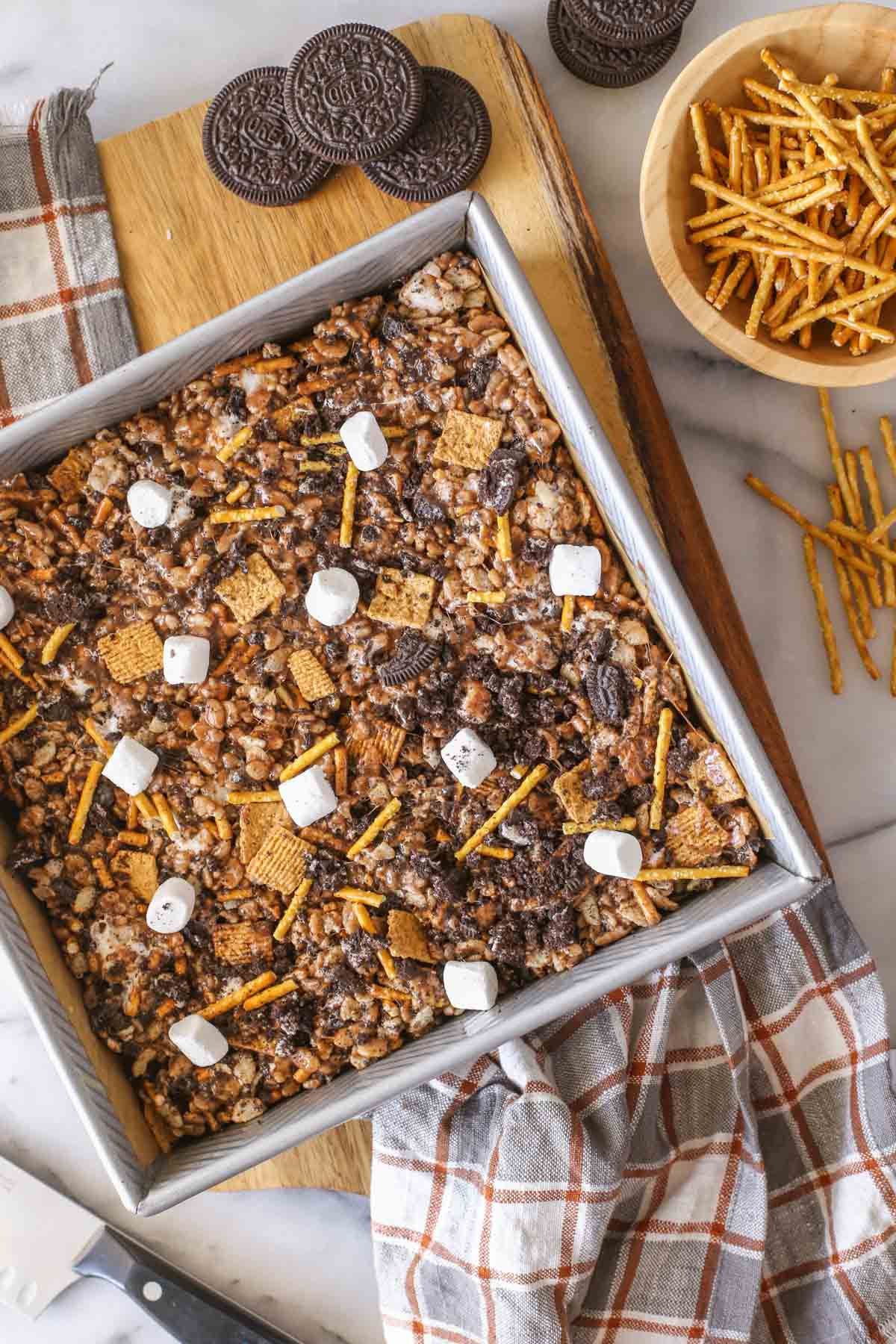 Overhead shot of a square pan of S'more Bars on a wood cutting board, with some whole Oreo cookies and a small wood bowl of pretzel sticks next to it.