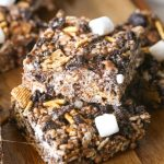 Close up shot of two S'more Bars stacked on a wood cutting board with more bars in the background.