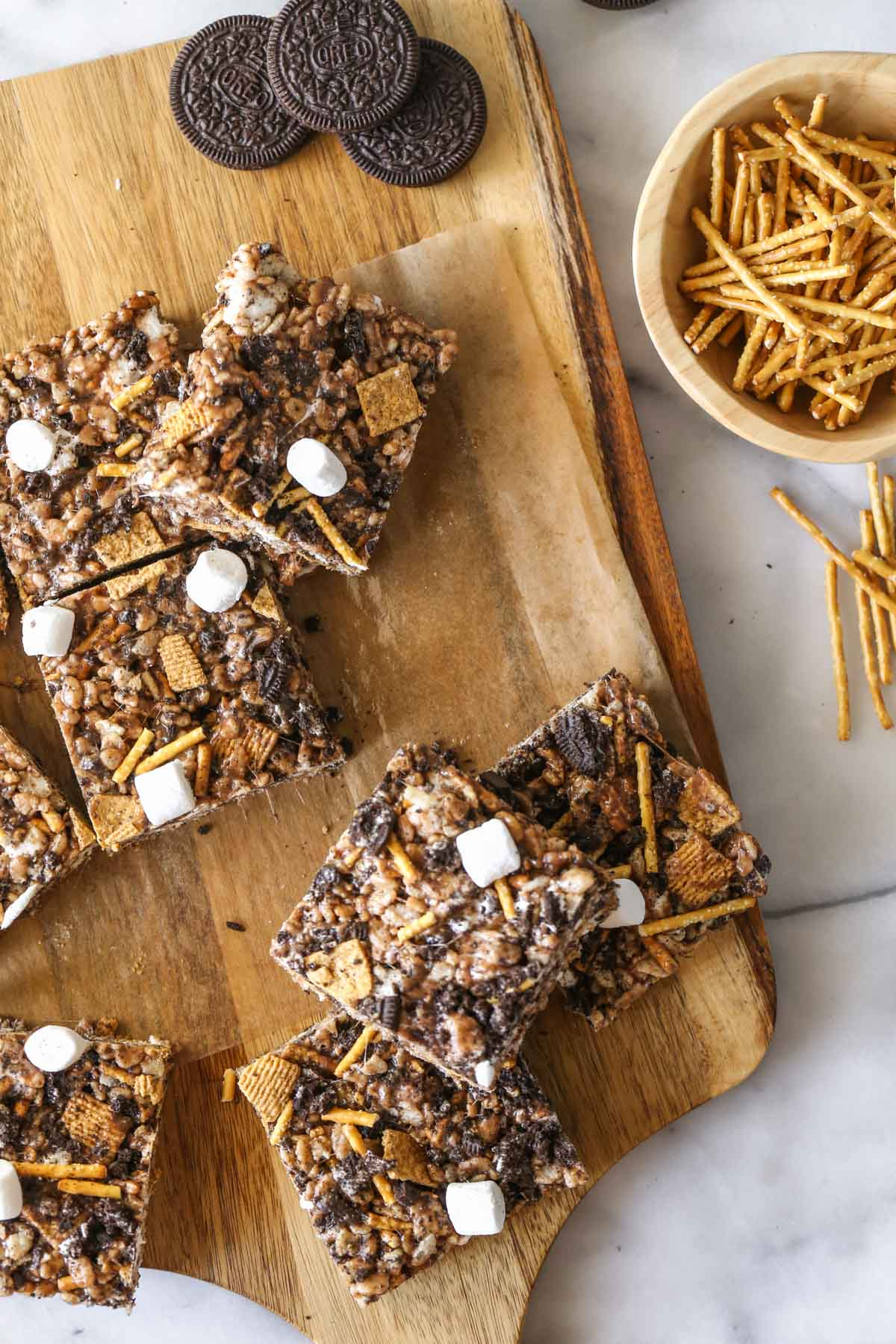 Overhead shot of cut S'more Bars on parchment paper on a wood cutting board, with some whole Oreo cookies and a small wood bowl of pretzel sticks next to it.