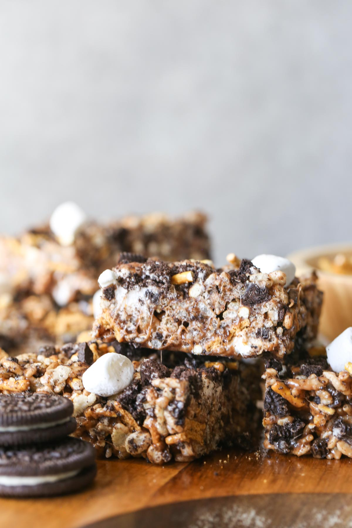 Close up shot of three cut S'more Bars stacked on a wood cutting board with two whole Oreo cookies stacked next to them.