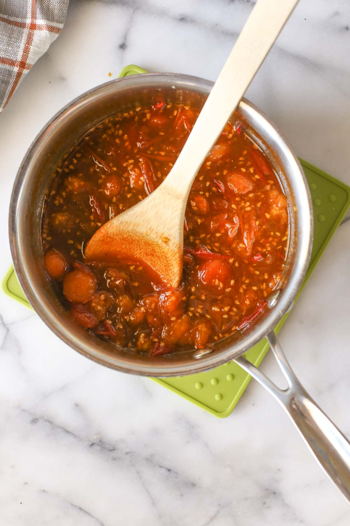 Overhead shot of Tomato Jam in a saucepan during the cooking process with a wooden spoon in it.