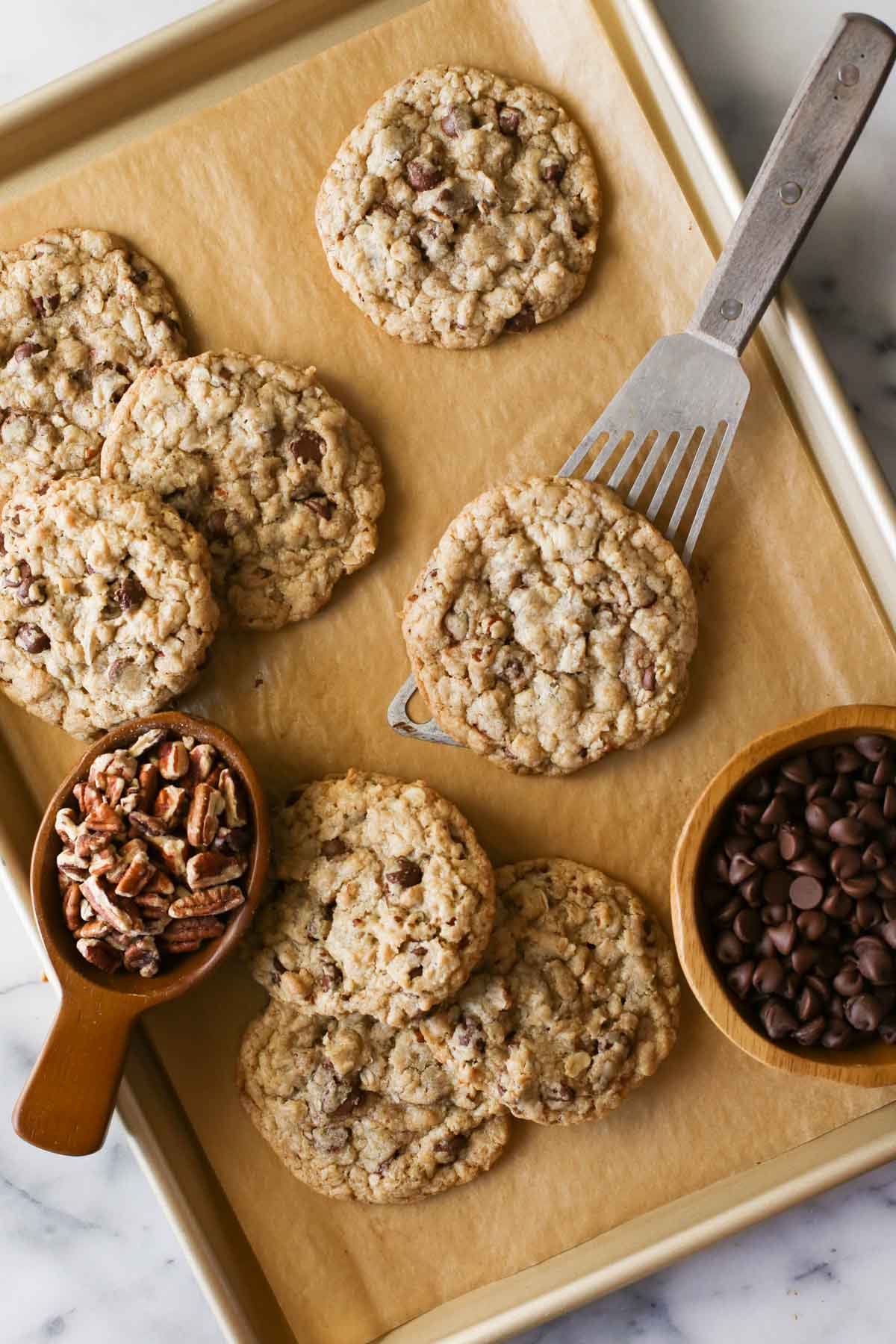 Overhead shot of Cowboy Cookies on a parchment paper lined baking sheet, along with a wood scoop full of pecans and a wood bowl of chocolate chips, and a spatula under one of the Cowboy Cookies.