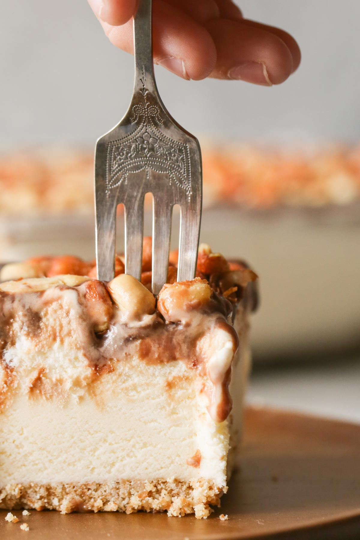 A close up of a fork sticking in a piece of Peanut Buster Ice Cream Dessert.   The layers of the Nilla Wafer crust, vanilla ice cream, chocolate fudge, and Spanish peanuts are distinguishable.