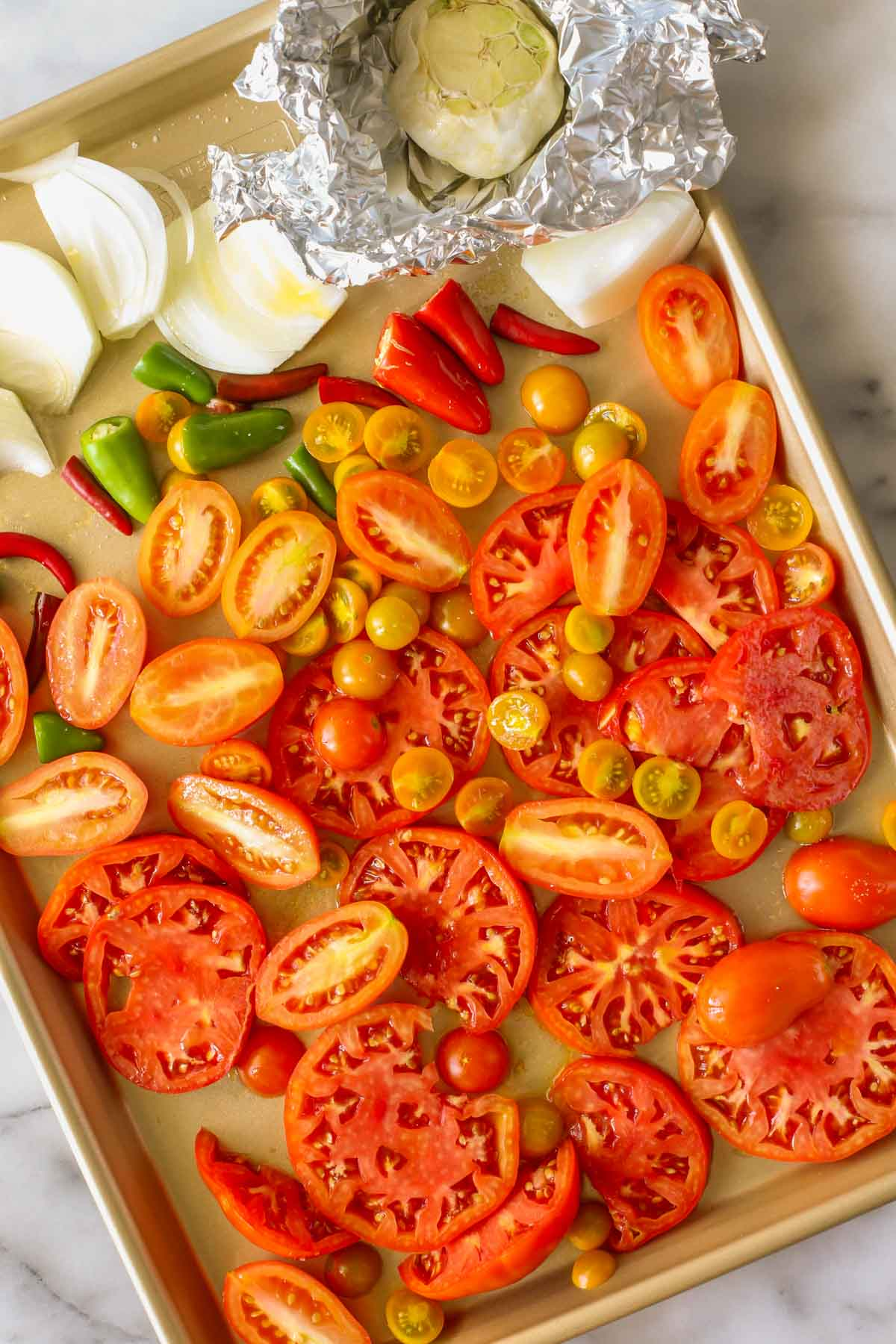 Overhead shot of tomatoes, peppers, onions, and garlic on a sheet pan, all ingredients for Roasted Tomato Salsa.