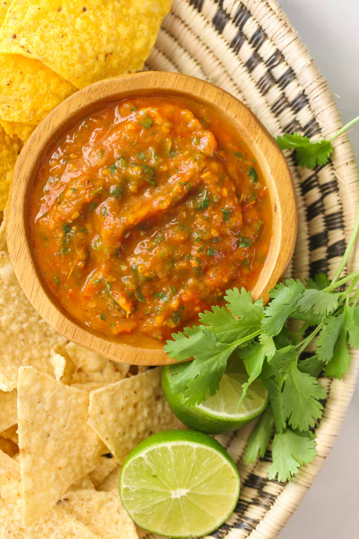 Close up shot of a small wood bowl of Roasted Tomato Salsa in a basket along with tortilla chips, fresh cilantro, and two lime halves.