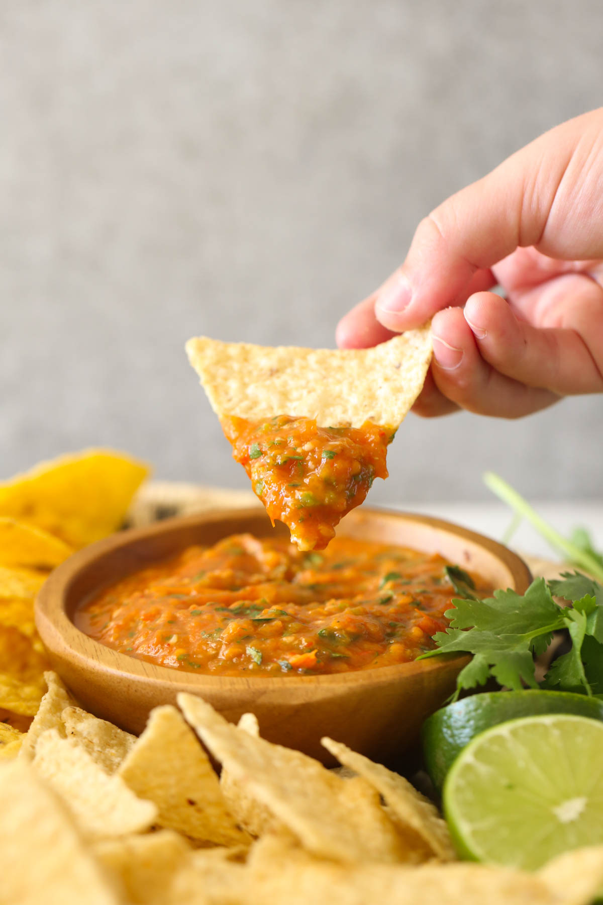 A hand holding a tortilla chip with Roasted Tomato Salsa on it above a small wood bowl of Roasted Tomato Salsa with tortilla chips, two lime halves and fresh cilantro next to the bowl.
