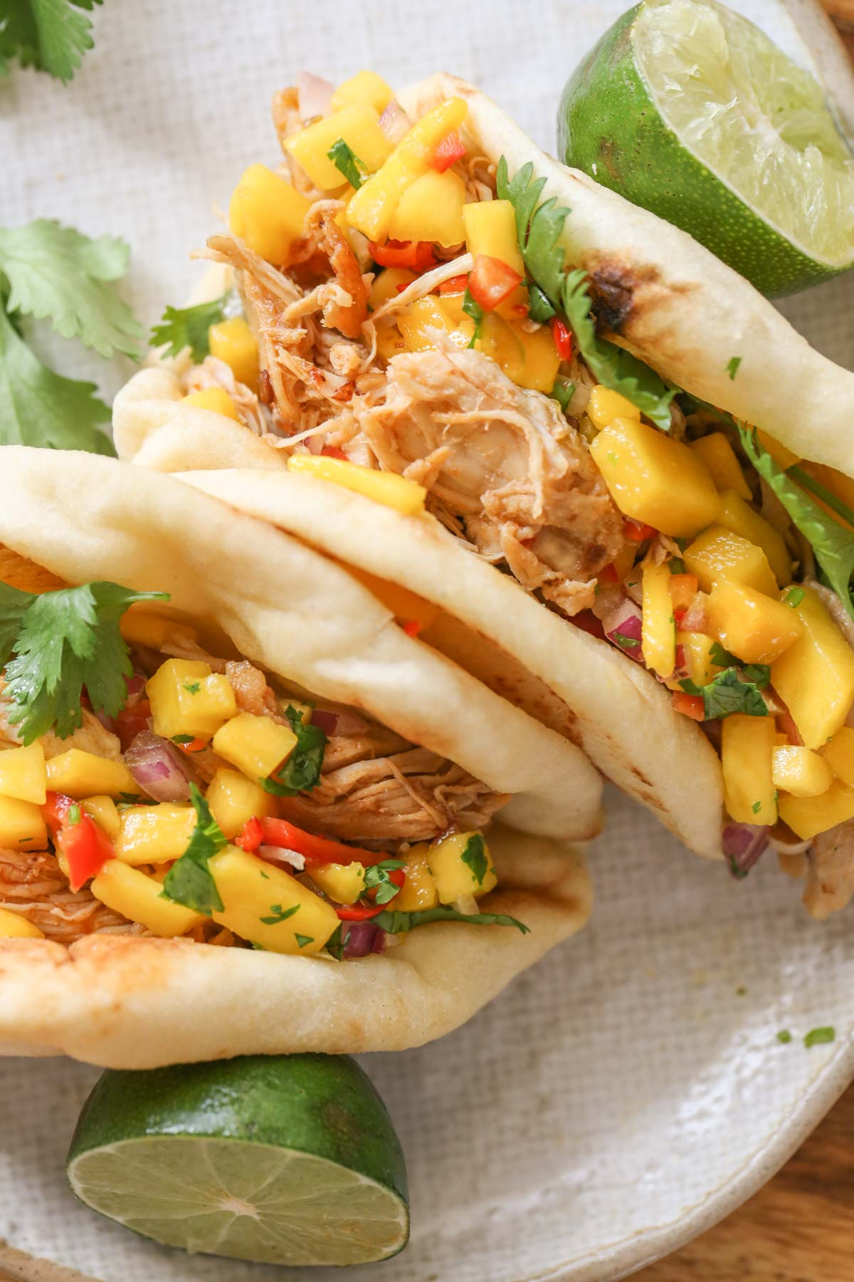 Close up overhead shot of two pieces of toasted naan bread filled with Buttery Honey Chipotle Chicken and topped with Mango Lime Salsa on a plate with a lime sliced in half and fresh cilantro.
