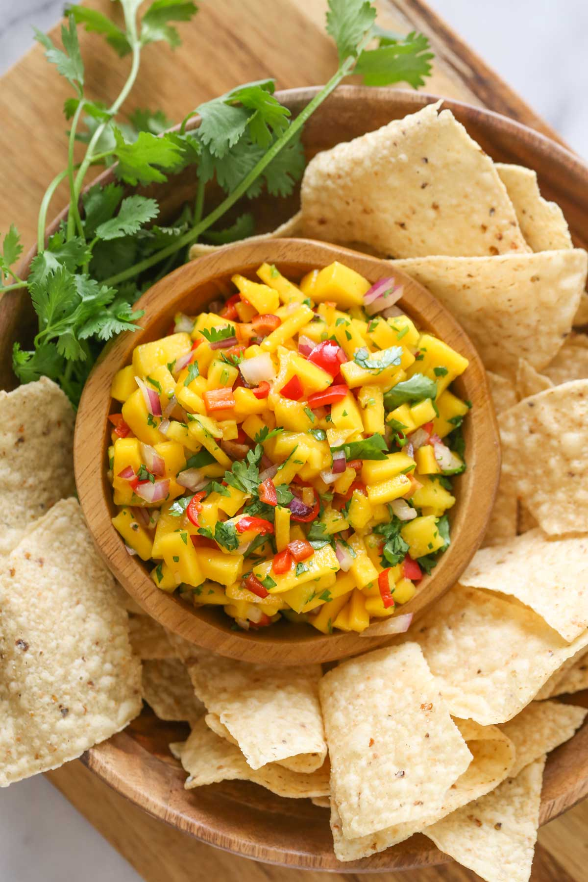 Overhead shot of a wood bowl of Mango Lime Salsa sitting inside a larger wood bowl with tortilla chips and fresh cilantro, all sitting on a wood cutting board.