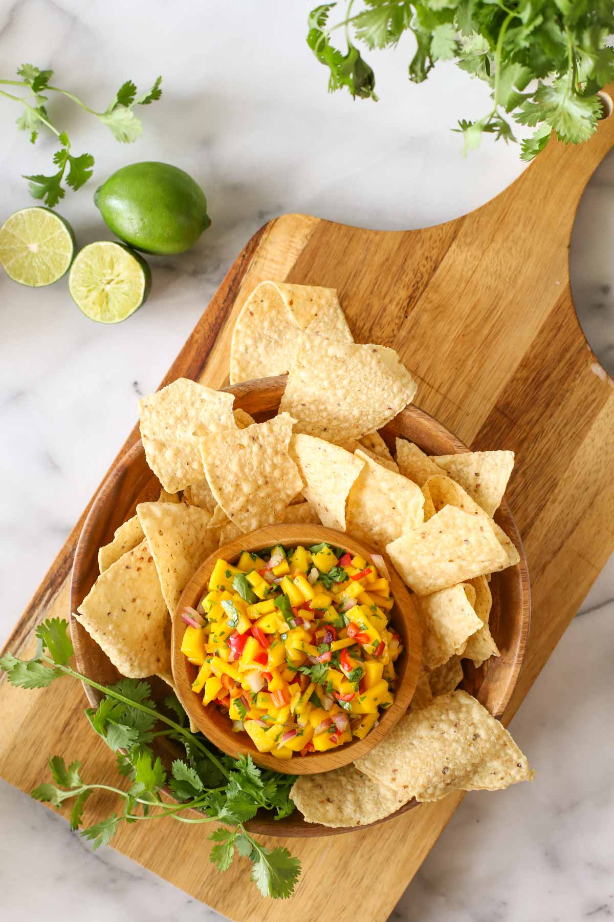 Overhead shot of a wood bowl of Mango Lime Salsa sitting inside a larger wood bowl with tortilla chips and fresh cilantro, all sitting on a wood cutting board with limes and cilantro next to it, all on a marble background.