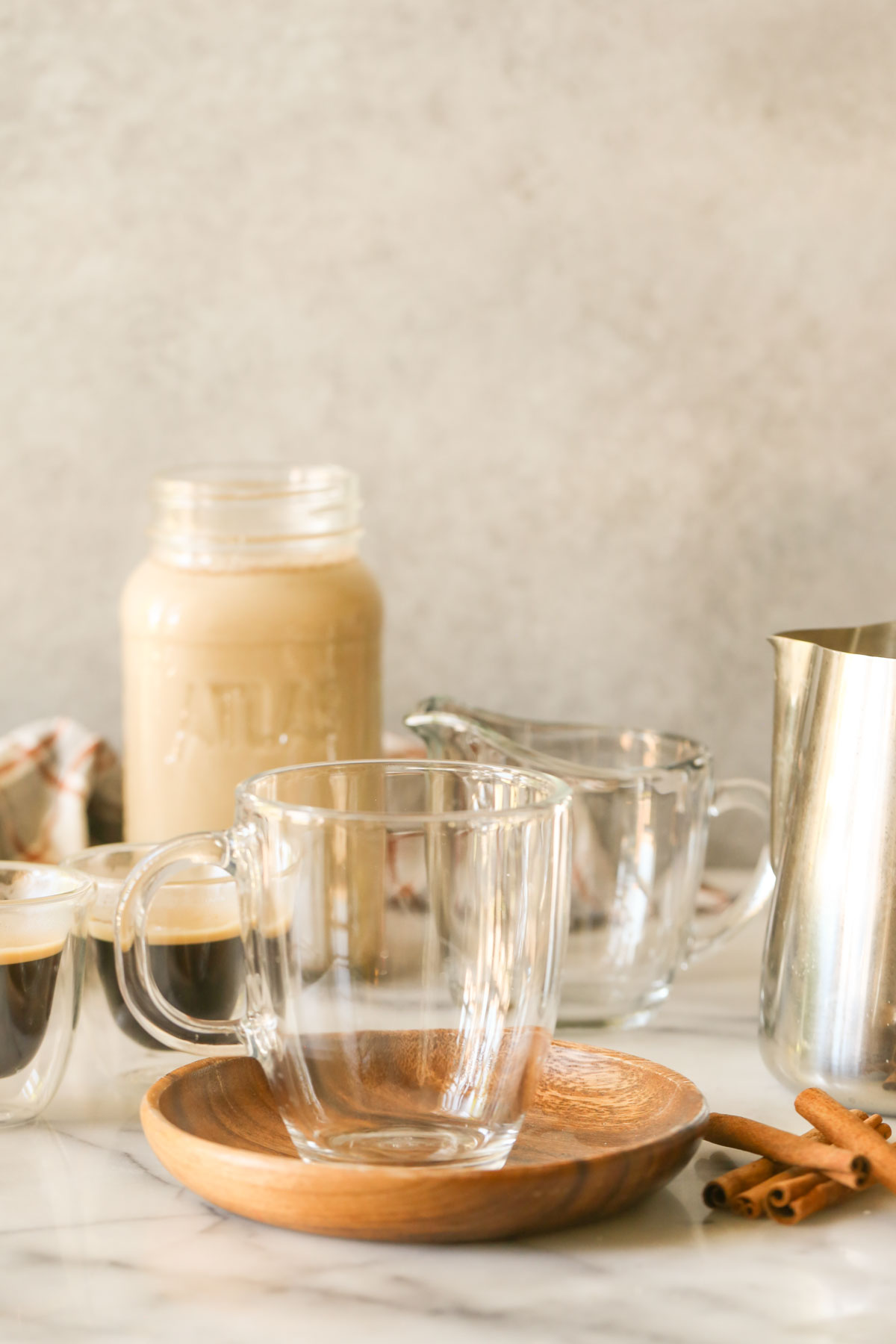 A glass mug on a wood saucer with cinnamon sticks next to it, espresso shots in the background, along with a glass jar of Brown Sugar and Cinnamon Coffee Creamer, a glass pouring mug and a stainless steel pitcher of steamed milk.