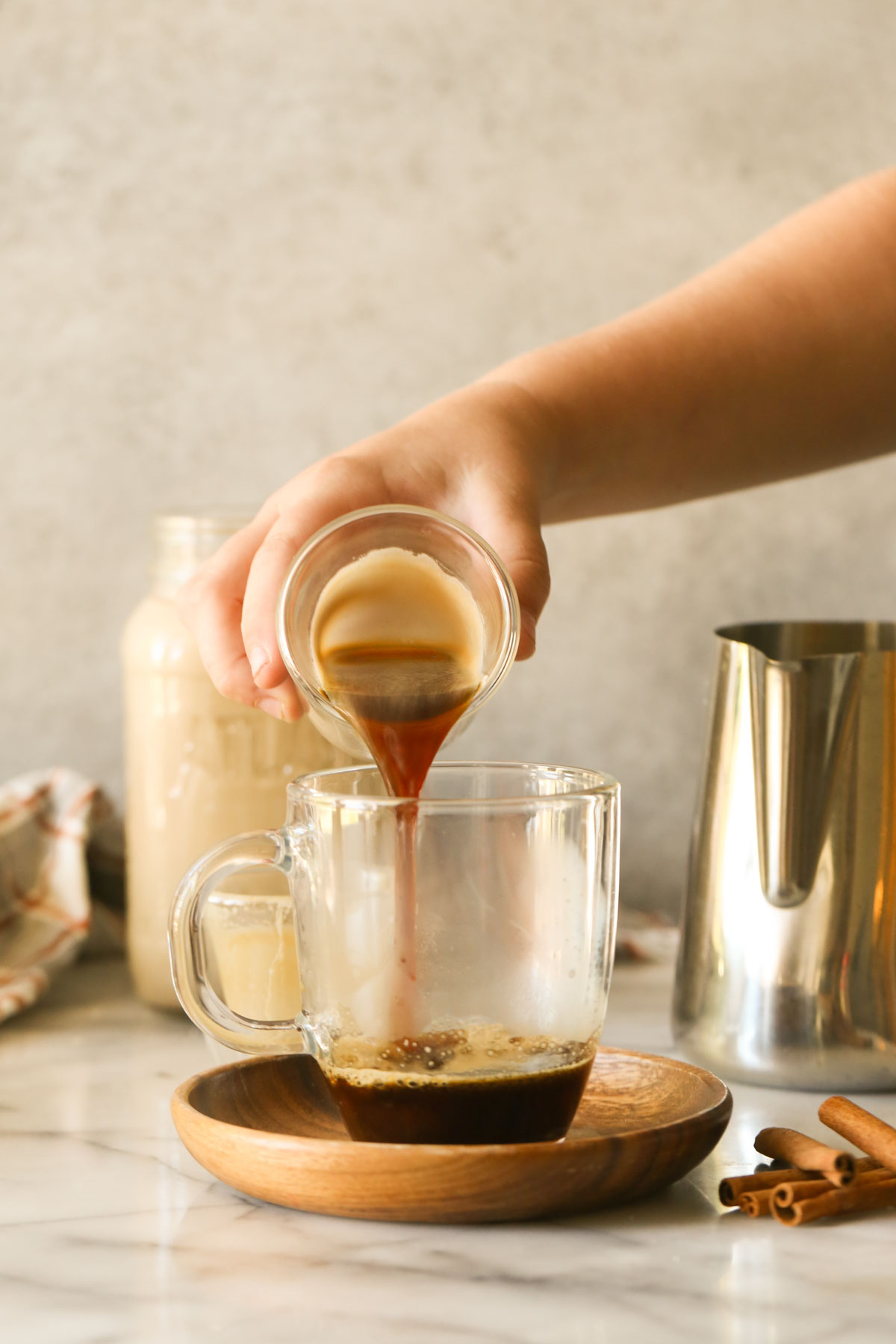 A hand pouring an espresso shot into a glass mug on a wood saucer with cinnamon sticks next to it, with a glass jar of Brown Sugar and Cinnamon Coffee Creamer and a stainless steel pitcher of steamed milk in the background.