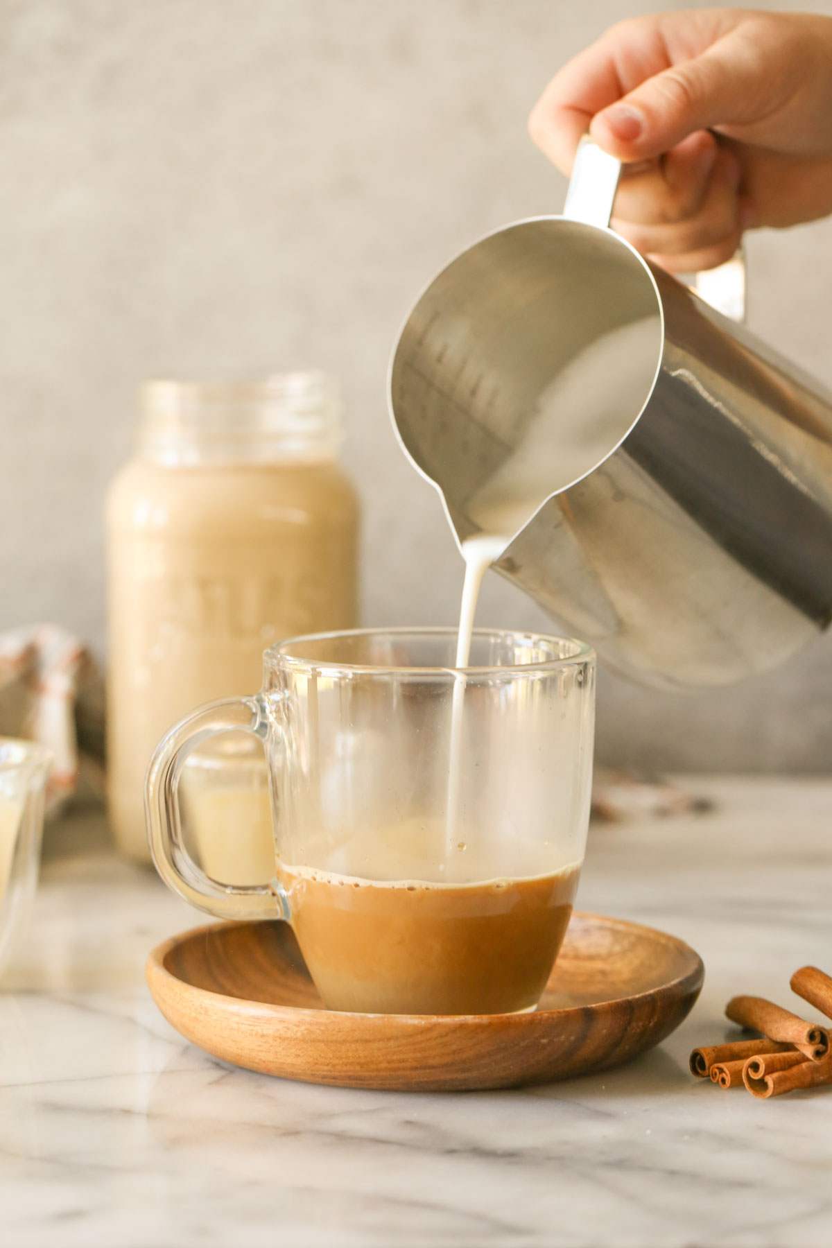 A hand pouring steamed milk from a stainless steel pitcher into a glass mug with espresso in it, sitting on a wood saucer with cinnamon sticks next to it, with a glass jar of Brown Sugar and Cinnamon Coffee Creamer in the background.