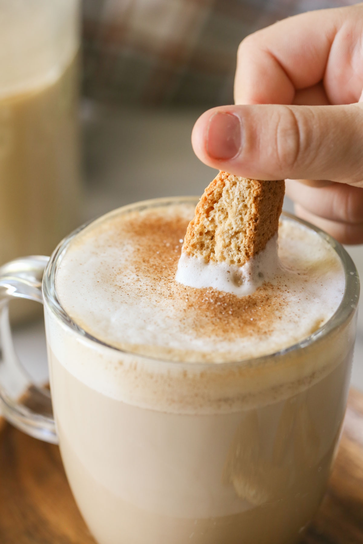 A close up shot of a hand dipping biscotti into a latte in a glass mug, that has Brown Sugar and Cinnamon Coffee Creamer in it and has been dusted with cinnamon and sugar.