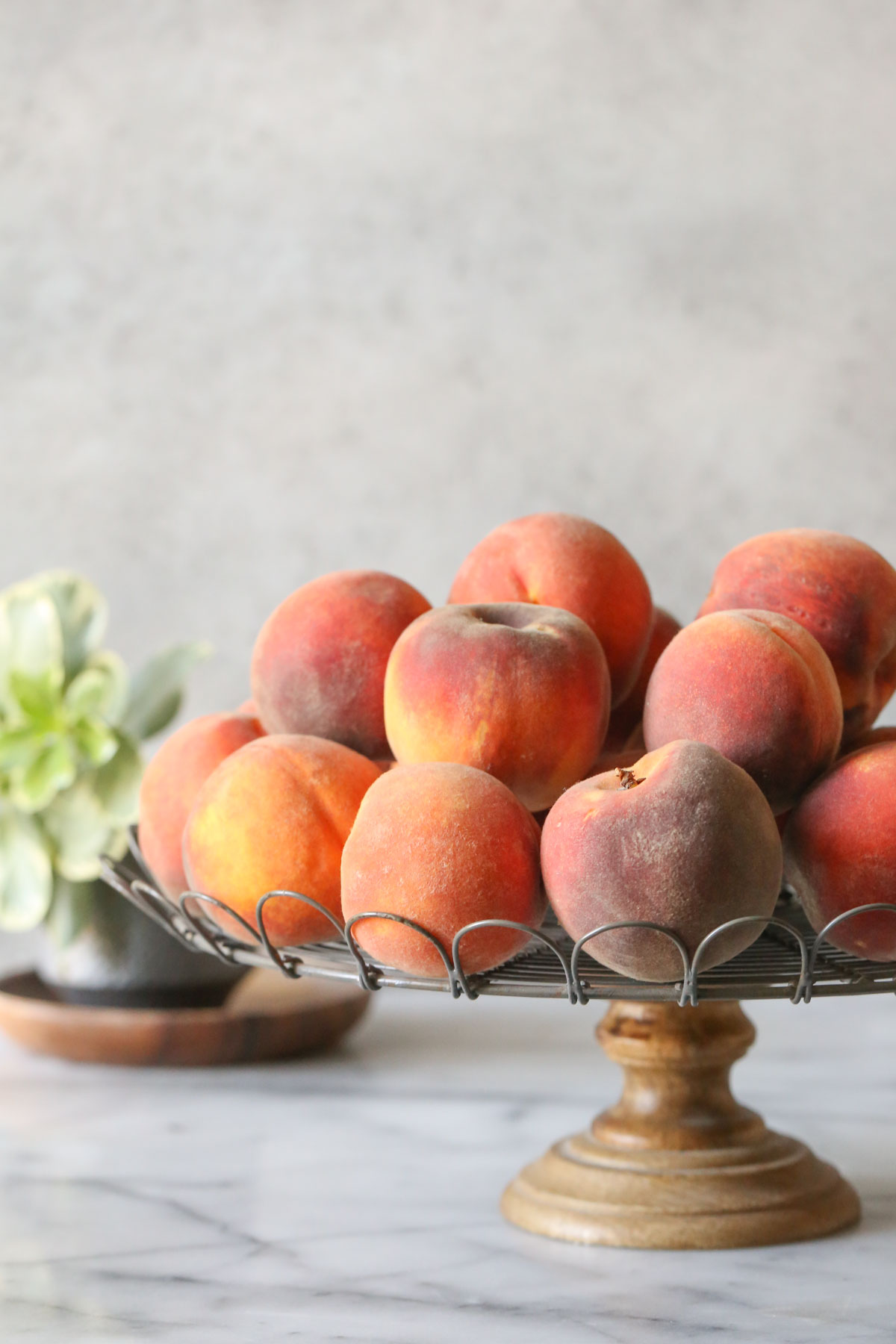 A cake stand with peaches piled on top of it.